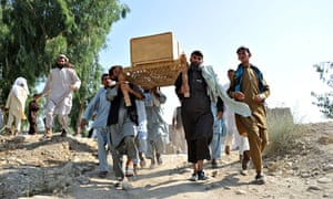 Afghan men carry a coffin