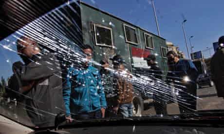 Egyptian security forces look at the shattered windscreen of a vehicle damaged in the Giza bombings