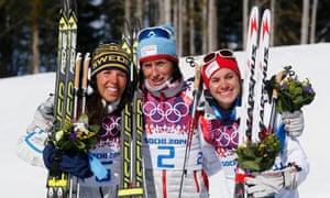 Norway's gold medal winner Marit Bjoergen is flanked by Sweden's silver medal winner Charlotte Kalla, left, and the bronze medal winner Heidi Weng.