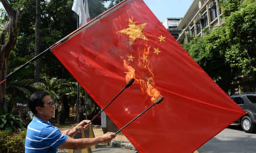 An activist burns a Chinese flag in the Philippines, which is one of the countries in dispute with China over the South China Sea
