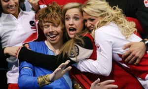 Kevin Reynolds of Canada reacts with fellow team members as his result is announced in the men's team free skate figure skating competition at the 2014 Winter Olympics.