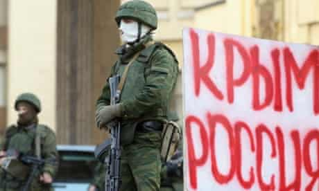 """Soldiers, believed to be Russian, guard the Crimean parliament building on Saturday next to a sign that reads: """"Crimea Russia""""."""