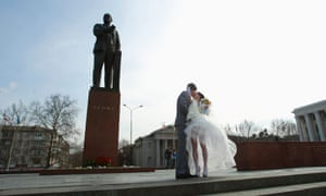 Life goes on. A newly married couple kiss under the statue of Lenin in Simferopol on Saturday.