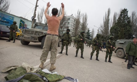 A Ukrainian soldier tries to persuade Russian troops to move away from a Ukrainian military base in Balaklava, Crimea on Saturday.
