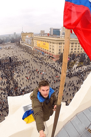 A protester replaces a Ukrainian flag with a Russian flag in Kharkiv