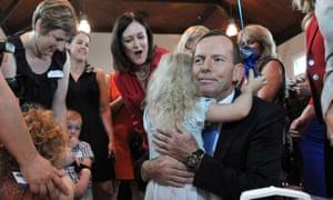 Tony Abbott hugs a young girl at an International Women's Day
