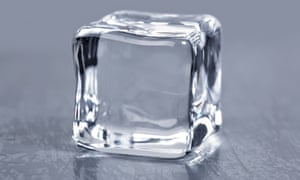 A completely transparent ice cube on a table