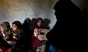 A Pakistani schoolgirl receives polio vaccine drops from a health worker
