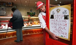 Butcher in red hat and apron puts sign on his door: Stop horsing around, use your local butcher!