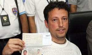 Italian Luigi Maraldi, left, whose stolen passport was used by a passenger boarding a missing Malaysian airliner, shows his passport as he reports himself to Thai police at Phuket police station in Phuket province.
