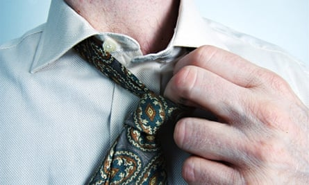 Stress at work: a man loosening his tie