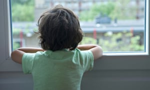 Lonely little boy looking out of the window