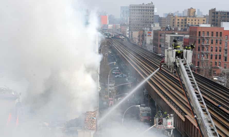 Firefighters battle a blaze at the site of an explosion and building collapse  in New York.