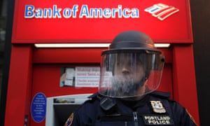 A policeman in riot gear defends a Bank of America as protesters march past various banks in Portland