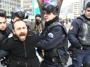 An anti-government protester is detained by riot policemen during a protest rally to mark the funeral of Berkin Elvan in Ankara
