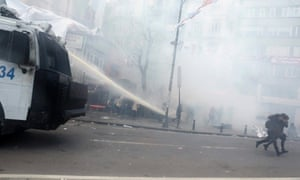 People run away as Turkish riot police uses water cannons and tear gas to disperse protesters during a rally for Berkin Elvan, in Istanbul, Turkey.