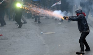 A protester uses fireworks during clashes with riot police at the funeral of Berkin Elvan in Istanbul.
