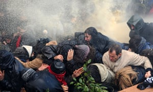 Protesters take cover from police water cannons during Berkin Elvan`s funeral on in Istanbul.