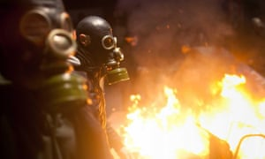 Protesters with gas masks to counter police tear gas pass flaming barriers as violence erupted during protests in Kadikoy neighbourhood of Istanbul, reacting to the death of Berkin Elvan.