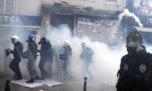 Protestors throw back tear gas canisters at the riot police during clashes at the funeral of Berkin Elvan in Istanbul.