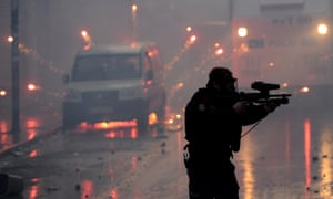 A policeman walks through debris as he fires rubber bullets into the crowd at the funeral of Berkin Elvan in Istanbul