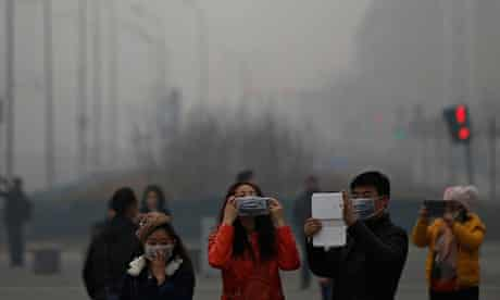 A woman adjusts her mask amid thick haze in Beijing
