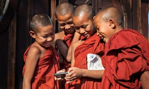 Young monks gathering around iphone