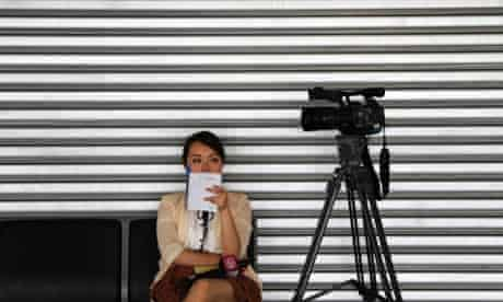 A reporter from China waits by her camera at the Kuala Lumpur International Airport as search planes continue to look for the missing Malaysia Airlines aircraft, Flight MH370.