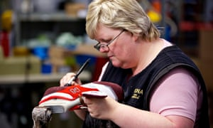 A woman works on a shoe at the New Balance factory in Flimby, Cumbria