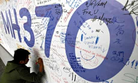 A man writes a message for passengers of Malaysian Airlines flight MH370 at Kuala Lumpur airport