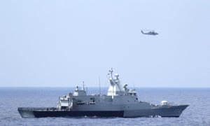The Royal Malaysian Navy corvette KD Terengganu and a U.S. Navy MH-60R Sea Hawk helicopter from the US Navy guided-missile destroyer USS Pinckney conduct a coordinated air and sea search for a missing Malaysian Airlines jet in the Gulf of Thailand March 12, 2014