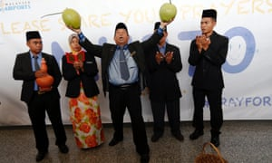 """Ibrahim Mat Zin  a local well-known """"bomoh"""", the Malay term for a shaman, holds two coconuts as he performs a ritual to help finding the missing Malaysia Airlines MH370 at Kuala Lumpur International Airport."""