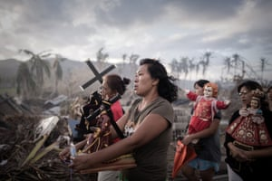 This photograph taken on November 18, 2013 shows survivors of Super Typhoon Haiyan marching in a religious procession in Tolosa on the eastern Philippine island of Leyte one week after the Super Typhoon devastated the area.