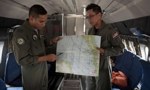 Royal Malaysian Air Force Navigator captain, Izam Fareq Hassan and pilot major Ahmad Shazwan Mohammed show locations on a map during a search and rescue operation to find the missing Malaysia Airlines flight MH370 plane over the Strait of Malacca.