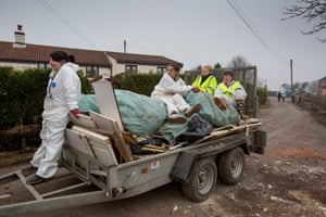 A truck loaded with volunteers arrives to pick up piles of plasterboard and rubble that resident Philip Maye had stacked up near the road