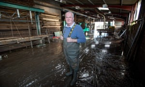Neil Craddock stands inside his wrecked wooden flood business in Somerset.