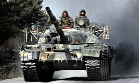Russian soldiers on top of a tank drive on a road near the flashpoint city of Gori on 18 August 2008