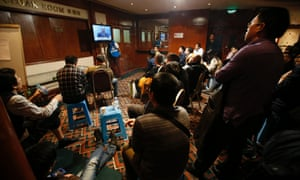 Family members of passengers aboard the missing Malaysia Airlines Flight MH370 watch Malaysia's Prime Minister Najib Razak speak during a news conference in Kuala Lumpur on Saturday.