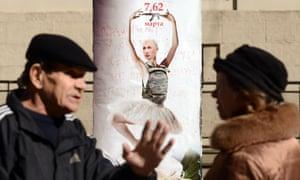 People speak in front of a placard depicting the Russian president, Vladimir Putin, as a dancing ballerina wearing a bulletproof vest with Kalashnikov machine gun.
