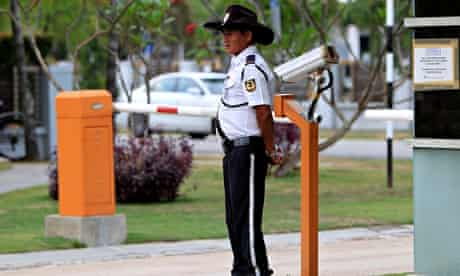 A security guard stands at a main gate outside the house of the missing Malaysia Airlines pilot