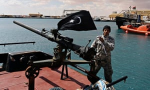 A rebel under Ibrahim Jathran holds the Cyrenaica flag while standing on a boat at Es Sider port.