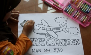 Eight-year-old Syira Nazia Hutabarat, from Medan in Indonesia,works on a picture praying for the Malaysia Airlines flight MH370 to return.