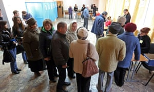 People line up to receive their ballots during the referendum on the status of Ukraine's Crimea region at a polling station in Simferopol