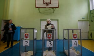 A woman casts her ballot during voting in a referendum at a polling station in Simferopol
