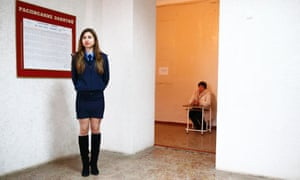 A Ukrainian police officer stands on duty during voting