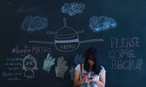 A woman uses her mobile phone as she stands against a chalkboard with messages for family members of passengers onboard the missing Malaysia Airlines Flight MH370, at an event to express solidarity in Subang Jaya March 16, 2014.