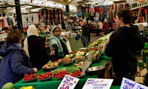 A fruit stall in Leicester Market with various ethnic groups