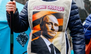 "A pro-Russia demonstrator wears a vest bearing a depiction of Russian President Vladimir Putin and the words, ""Motherland! Freedom!"" during a rally in Donetsk, Ukraine"
