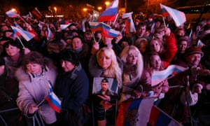 A woman holds a portrait of Russia's President Vladimir Putin as others wave Russian flags as the preliminary results of today's referendum are announced in the Crimean city of Sevastopol.