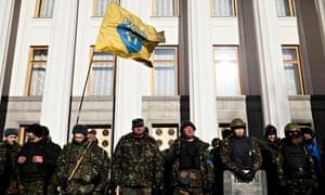 Men in camouflage gear line up outside the parliament in Kiev, Ukraine
